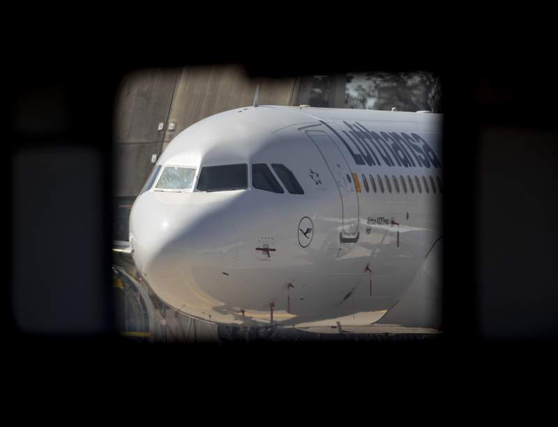 A parked Lufthansa aircraft is seen through a hangar window at the airport in Frankfurt, Germany, Thursday, July 30, 2020. Lufthansa were showing the media how manufacturing has been restarted after the break imposed by the coronavirus outbreak (AP Photo/Michael Probst)