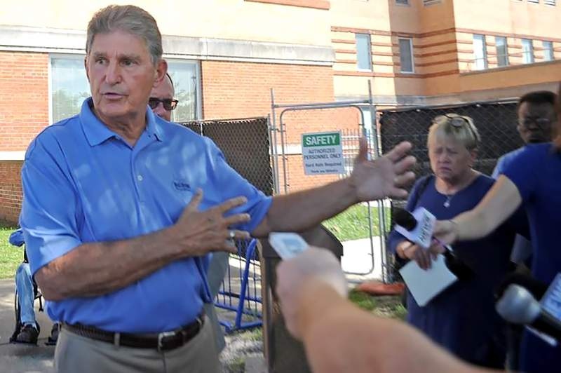 FILE - In this Aug. 30, 2019 file photo, U.S. Sen. Joe Manchin talks to reporters outside of the Louis A. Johnson VA Medical Center in Clarksburg, W.Va.  A woman is suing the federal government over the 2018 death of her father from a wrongful insulin injection at the West Virginia veterans hospital. Melanie Proctor filed the lawsuit Monday, March 2, 2020 against Veteran Affairs Secretary Robert Wilkie. It details a widespread system of failures at the Louis A. Johnson VA Medical Center in Clarksburg that led to the death of her father, former Army Sgt. Felix Kirk McDermott.(Eddie Trizzino/Times-West Virginian via AP, File)