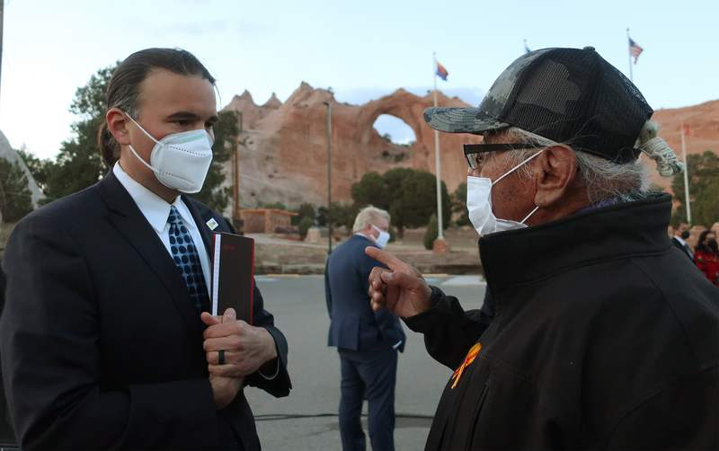FILE - In this April 22, 2021, file photo, Bryan Newland, left, speaks with Navajo Nation Council Delegate Daniel Tso in Window Rock, Ariz. President Joe Biden's nominee to oversee Indigenous affairs at the Interior Department said Wednesday, June 9, 2021, that he won't impede tribes as they seek to improve infrastructure, public safety and the economy on their lands. Newland appeared before the Senate Indian Affairs Committee where he received widespread support to become assistant secretary for Indian Affairs. (AP Photo/Felicia Fonseca, File)