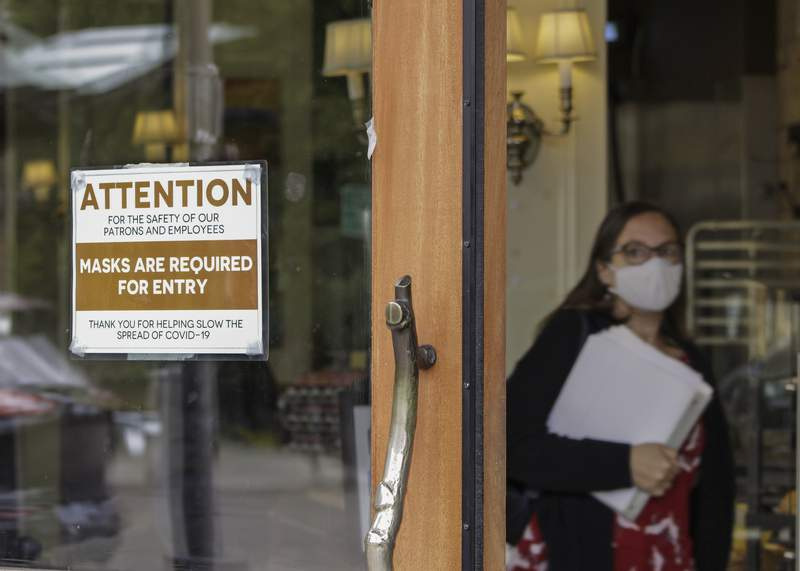 FILE - In this May 21, 2021 file photo, a sign reminds customers to wear their masks at a bakery in Lake Oswego, Ore. Oregon Gov. Kate Brown on Tuesday, Aug. 10, 2021 announced a statewide indoor mask requirement due to the spike in COVID-19 hospitalizations and cases, warning that the state's health care system could be overwhelmed. (AP Photo/Gillian Flaccus, File)