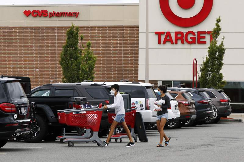 FILE - In this Aug. 4, 2020 file photo, shoppers take purchases to their vehicle in the parking lot of a Target store in Marlborough, Mass.  Targets strong sales streak extended through the holiday season, as shoppers snapped up everything from clothing to home goods during the pandemic. The Minneapolis company reported Wednesday, Jan. 13, 2021, that its online sales surged 102% for the November and December period. (AP Photo/Bill Sikes)