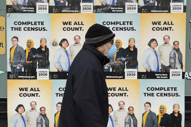 FILE - In this April 1, 2020, file photo, a man wearing a mask walks past posters encouraging participation in the 2020 Census in Seattle's Capitol Hill neighborhood. A delay in census data is scrambling plans in some states to redraw districts for the U.S. House and state legislatures. The Census Bureau has said redistricting data that was supposed to be provided to states by the end of March won't be ready until August or September. (AP Photo/Ted S. Warren, File)