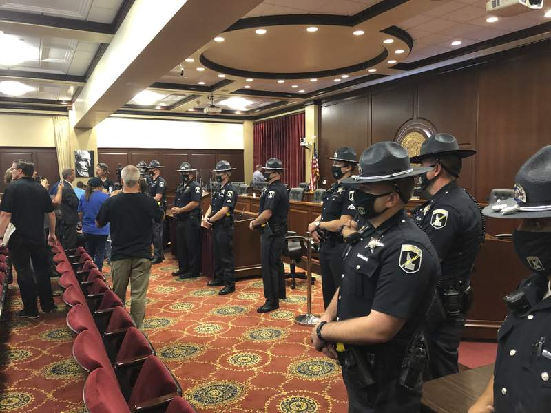Idaho State Police form a row in a committee meeting room in the Idaho Statehouse in Boise, Idaho, on Tuesday, Aug. 25, 2020. One person was taken into custody and lawmakers abandoned the room after spectators at a House committee meeting at the Idaho Statehouse became disruptive. The committee left the room as at least a dozen Idaho State Police formed a shield between them and the crowd of more than 100. (AP Photo/Keith Ridler)