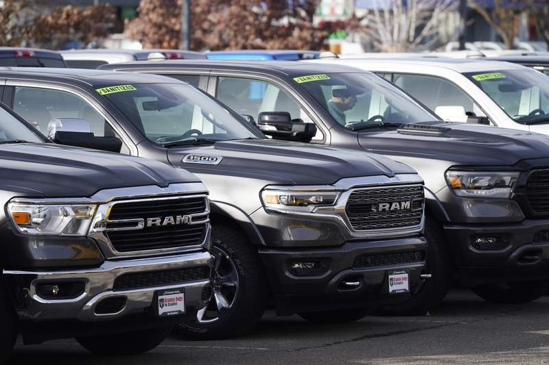 A long row of unsold 2020 pickup trucks sits at a Ram dealership Sunday, Dec. 27, 2020, in Littleton, Colo.  A new government report says gas mileage for new vehicles dropped and pollution increased in model year 2019 for the first time in five years.  (AP Photo/David Zalubowski)