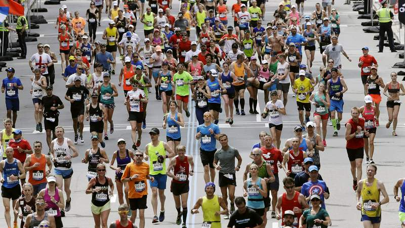 FILE - In this April 17, 2017, file photo, runners head down the stretch to the finish line in the 121st Boston Marathon in Boston. Rival camps in the running world began snapping at each other's heels in March 2021 after the Boston Athletic Association, which still hopes to hold a truncated in-person edition of the footrace in October, said it would award medals to up to 70,000 athletes if they go the distance wherever they are. (AP Photo/Charles Krupa, File)