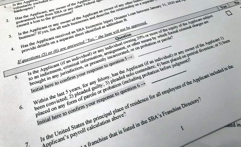Shown is a portion of a Small Business Administration Paycheck Protection Program Borrower Application Form, Tuesday, April 21, 2020 in Washington. The Paycheck Protection was supposed to be a lifeline for small businesses, helping them stay afloat and keep their employees on the payroll during the coronavirus pandemic. But guidelines from the Small Business Administration say that businesses are ineligible if someone who owns at least 20 percent of the company is incarcerated, under indictment, on probation or parole or had been convicted of a felony within the last five years. Ineligible would-be applicants and advocates say the restrictions are a slap in the face for those who have served their time, especially from an administration that has trumpeted second chances.(AP Photo/Wayne Partlow)
