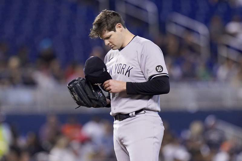 New York Yankees starting pitcher Jordan Montgomery removes his cap after giving up a double to Miami Marlins' Miguel Rojas during the first inning of a baseball game, Sunday, Aug. 1, 2021, in Miami. (AP Photo/Lynne Sladky)
