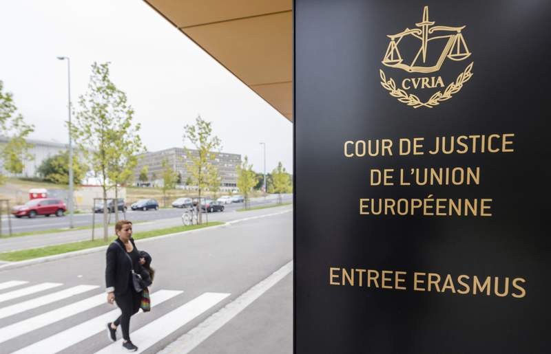 FILE - In this file photo taken on Monday, Oct. 5, 2015 a woman walks by the entrance to the European Court of Justice in Luxembourg. The European Union is referring Poland to Europes top court over long-standing concerns about respect for the rule of law and the independence of the countrys Supreme Court judges. The blocs executive commission had previously warned Poland that it might go to the European Court of Justice if the government did not take action to fix the problems. The EUs justice commissioner on Wednesday, March 31, 2021 called the court referral a crucial step in the infraction process against Poland. (Geert Vanden Wijngaert, File)