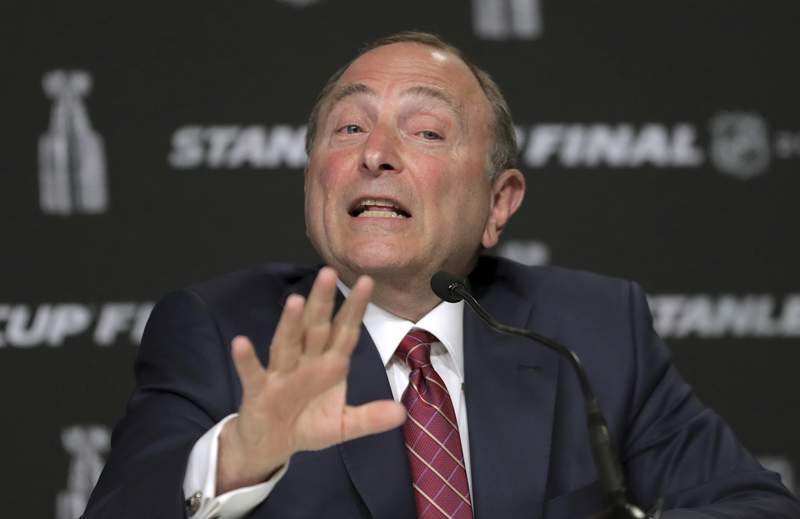 FILE - In this May 27, 2019, file photo, NHL Commissioner Gary Bettman speaks to the media before Game 1 of the NHL hockey Stanley Cup Final between the St. Louis Blues and the Boston Bruins in Boston. Bettman said getting to those quarantined bubbles and resuming play are just two more steps in the process with the goal of awarding the Stanley Cup in late September or early October. (AP Photo/Charles Krupa, File)