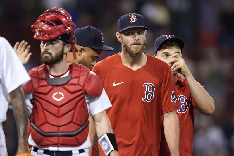 Boston Red Sox pitcher Chris Sale, center, who is on the disabled list, walks with teammates after a 20-8 win against the Tampa Bay Rays after a baseball game at Fenway Park, Wednesday, Aug. 11, 2021, in Boston. (AP Photo/Charles Krupa)