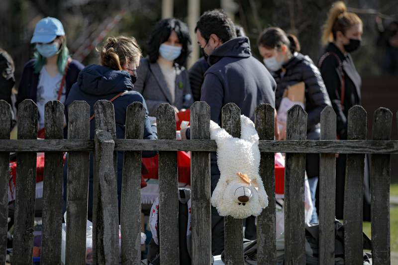 A teddy bear hangs from a fence at a spring charms fair at the Dimitrie Gusti Village Museum in Bucharest, Romania, Sunday, Feb. 28, 2021. (AP Photo/Vadim Ghirda)