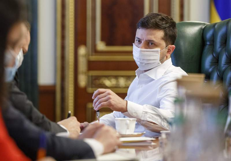 Ukrainian President Volodymyr Zelenskiy in a face mask to protect against coronavirus, discusses the COVID-19 situation in the country with officials in his office in Kyiv, Ukraine, Wednesday April 22, 2020. (Ukrainian Presidential Press Office via AP)