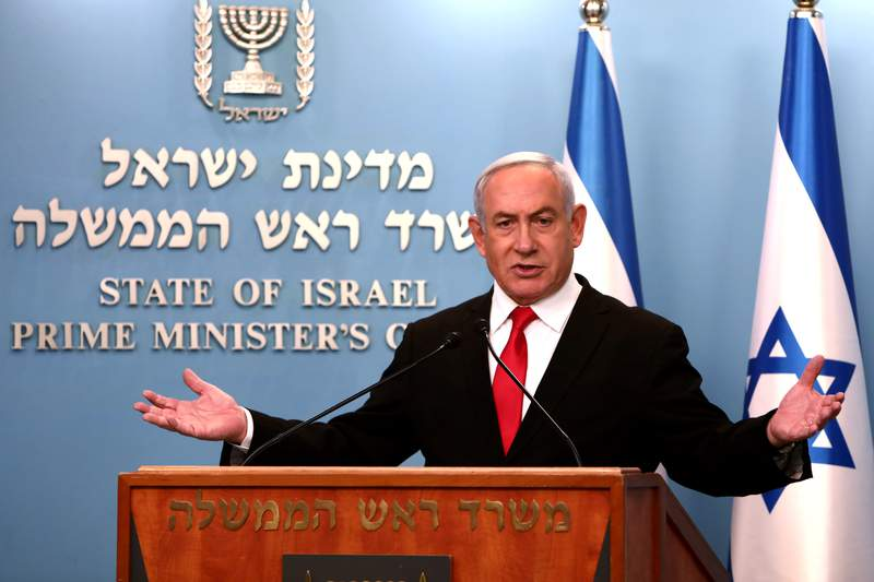 Prime Minister Benjamin Netanyahu delivers a speech from his Jerusalem office on Saturday, March 14, 2020, saying Israel's restaurants and places of entertainment will be closed to stop the spread of the coronavirus. He also encouraged people not to go to their workplaces unless absolutely necessary. (Gali Tibbon/Pool via AP)