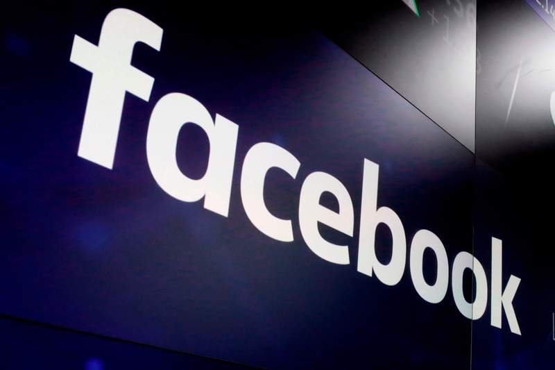 FILE - In this March 29, 2018, file photo, the logo for Facebook appears on screens at the Nasdaq MarketSite in New York's Times Square.  Academics, journalists and First Amendment lawyers are rallying behind New York University researchers in a showdown with Facebook over its demand that they halt the collection of data on political ads-targeting on the worlds dominant social media platform.  (AP Photo/Richard Drew, File)