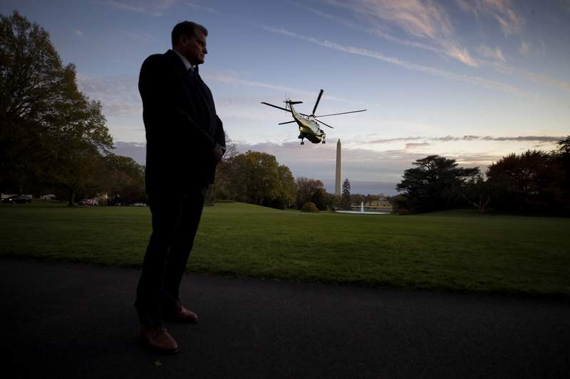 FIlE - In this Nov. 14, 2019, file photo a U.S. Secret Service special agent stands as Marine One, with President Donald Trump aboard, lifts off from the South Lawn of the White House in Washington. The White House is throwing its support behind a plan to relocate the U.S. Secret Service in order to better focus on the growing threat of online financial crimes. Shifting the agency from within the Department of Homeland Security to the Treasury Department would require action from Congress. (AP Photo/Alex Brandon, File)
