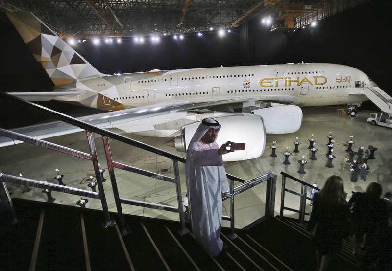 """FILE- In this Thursday, Dec. 18, 2014 file photo, an Emirati man takes a selfie in front of a new Etihad Airways A380 in Abu Dhabi, United Arab Emirates. Abu Dhabi's long-troubled national carrier Etihad on Thursday, March 5, 2020, reported losses of $870 million in 2019 after losing billions in recent years, calling the result """"encouraging."""" (AP Photo/Kamran Jebreili, File)"""