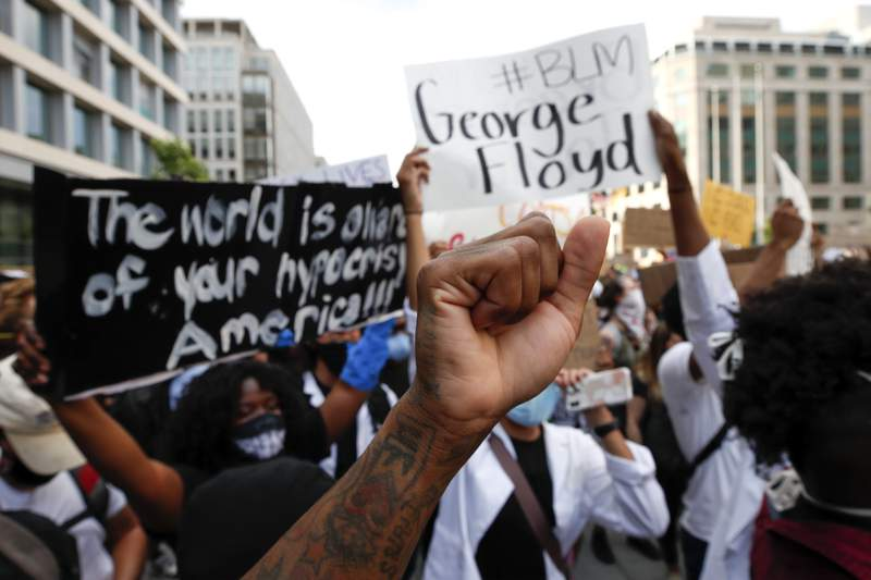 FILE - In this June 3, 2020, file photo, demonstrators gather near the White House in Washington to protest the death of George Floyd. A report released Thursday, July 15, 2021, says more than 90% of donors who supported racial equity initiatives in 2018 have yet to report how much they gave in 2020. (AP Photo/Alex Brandon, File)