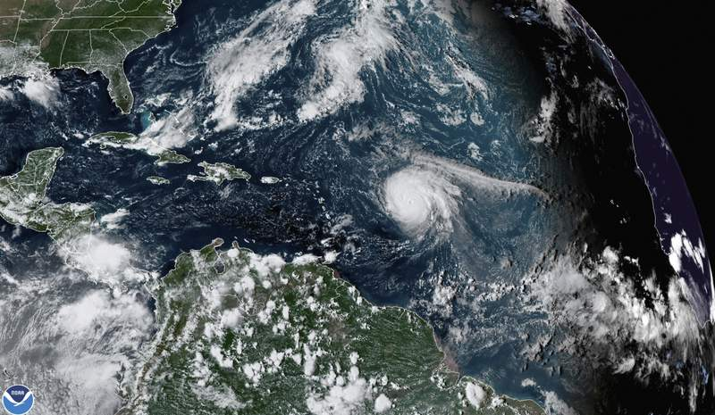 This satellite image provided by the National Oceanic and Atmospheric Administration shows Hurricane Sam, just right of center, in the Atlantic Ocean, Monday, Sept. 27, 2021, at 1920 Zulu (3:20 p.m. ET). Sam is a powerful Category 4 storm but it poses no threat to land as it loops northward in the Atlantic, according to the U.S. National Hurricane Center. (NOAA via AP)