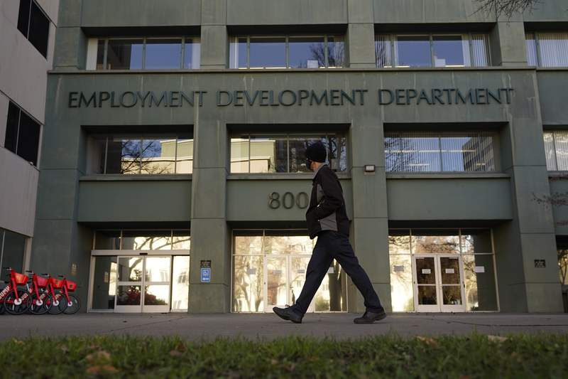 FILE - In this Dec. 18, 2020, file photo, a person passes the office of the California Employment Development Department in Sacramento, Calif. The recession that broke out with onset of the coronavirus pandemic officially ended in April 2021, making it the shortest downturn on record, according to the committee of economists that determines when recessions begin and end. (AP Photo/Rich Pedroncelli, File)