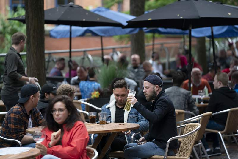 Members of the public are seen at a bar on Canal Street in Manchester's gay village, England, Saturday July 4, 2020. England is embarking on perhaps its biggest lockdown easing yet as pubs and restaurants have the right to reopen for the first time in more than three months. In addition to the reopening of much of the hospitality sector, couples can tie the knot once again, while many of those who have had enough of their lockdown hair can finally get a trim. (AP Photo/Jon Super)