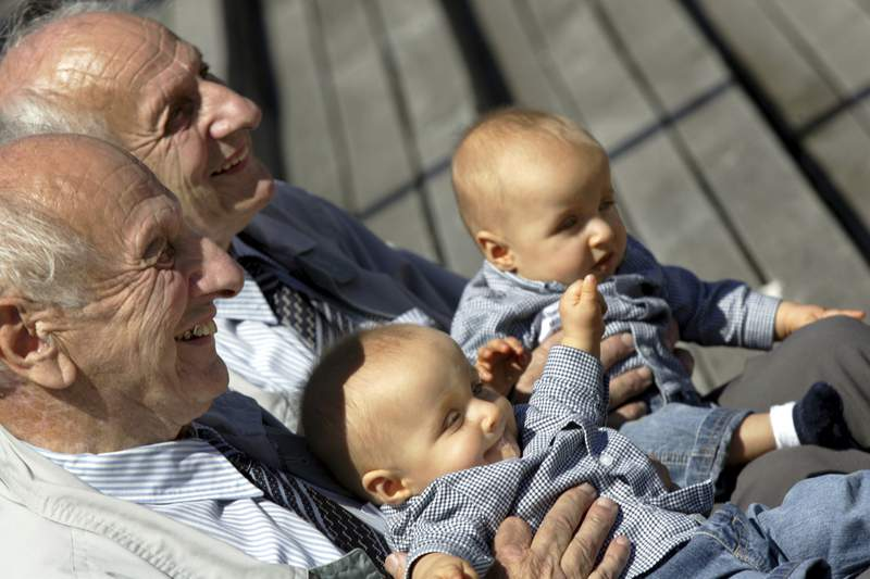 FILE - In this Saturday, June 18, 2005 file photo, identical twins Alf, left, and Sven Fehnhanhn, left background, 79, from Kassel, pose along with seven-month-old Luis Carl, right, und Albert Frank Millgramm, right background, during a twins' meeting in Berlin. According to research published on Thursday, Jan. 7, 2021, identical twins are not exactly genetically the same. (AP Photo/Jockel Finck)