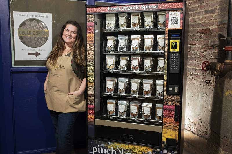 This March 10, 2021 photo shows Meaghan Thomas, co-owner of Pinch Spice Market, with a vending machine the company installed outside its Louisville, Ky. factory to make sales easier during COVID-19.  The vending machines helped the company cater to customers as it struggled through the COVID-19 pandemic. Its now a permanent addition. (Cornetet Fusion Photography/Pinch Spice Market via AP)