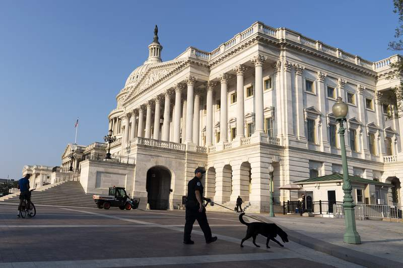 The U.S. Capitol is seen in Washington, early Tuesday, July 27, 2021, as U.S. Capitol Police watch the perimeter. Democrats are launching their investigation into the Jan. 6 Capitol insurrection. They're beginning with a focus on the law enforcement officers who were attacked and beaten as the rioters broke into the building. It's an effort to put a human face on the violence of the day. The police officers who are testifying Tuesday endured some of the worst of the brutality. The panel's first hearing comes as partisan tensions have only worsened since the insurrection. Many Republicans have played down or outright denied the violence that occurred and denounced the Democratic-led investigation as politically motivated. (AP Photo/Jose Luis Magana)